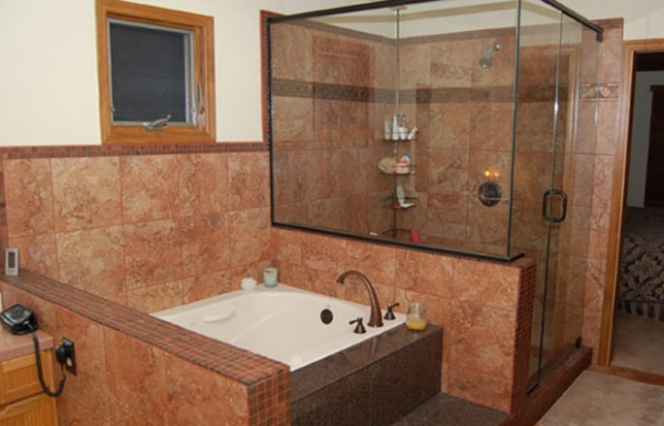 Smaller bath next to glass shower